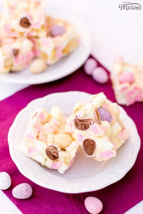 2 bars of mini egg rocky road on a white plate with mini eggs scattered around
