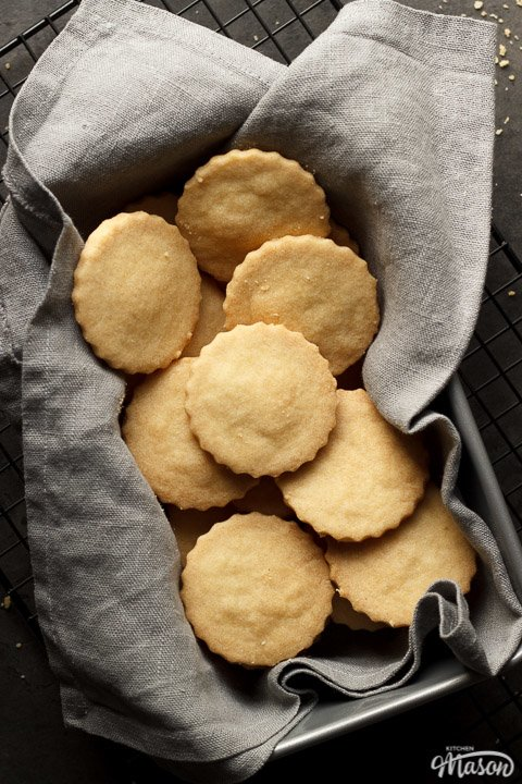 shortbread cookies in a tin lined with a grey cloth