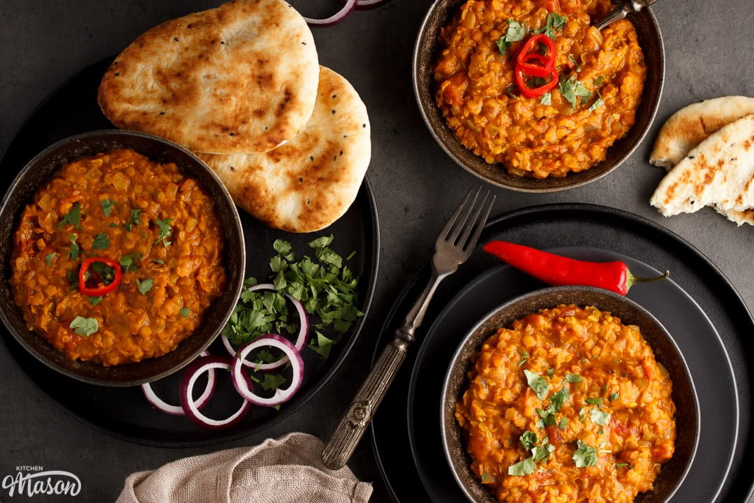 Lentil dahl in a black bowl topped with coriander and red chilli with naan bread & red onion on the side