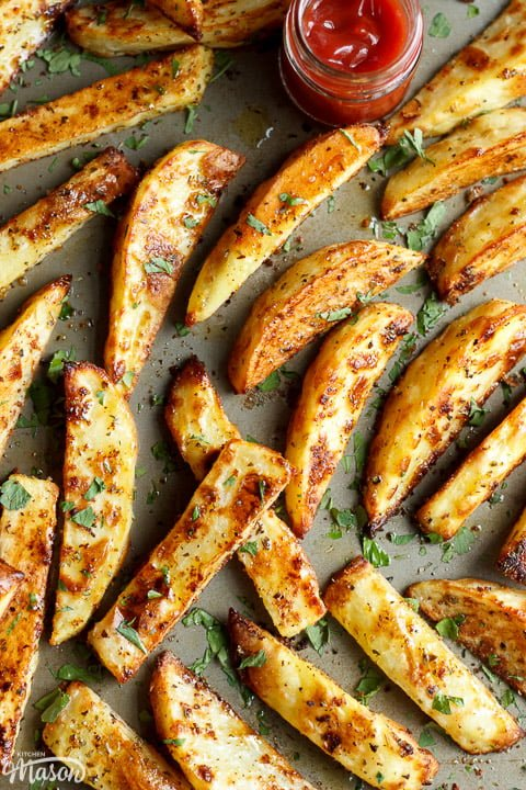 homemade wedges on a baking tray with fresh parsley scattered on top