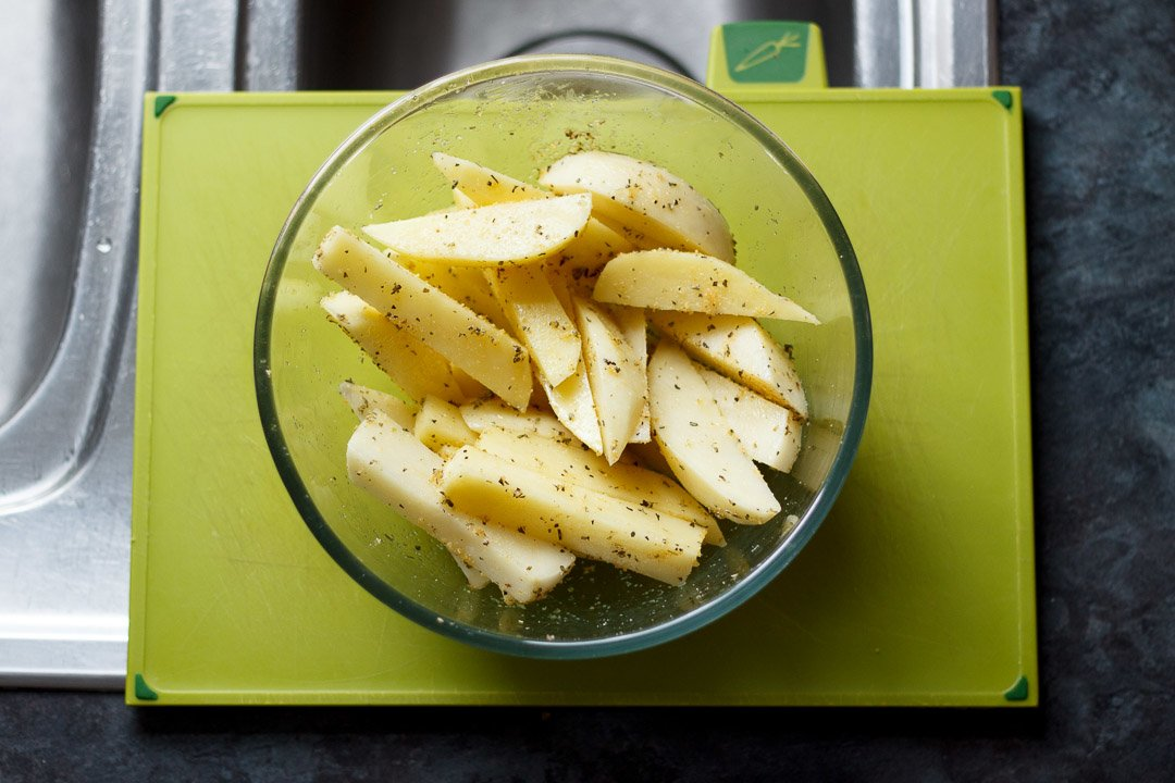 cut washed and dried potato wedges in a glass bowl with herbs and oil mixed through