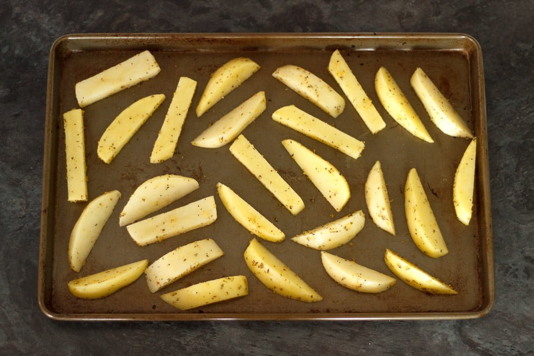 prepared potato wedges on a baking tray
