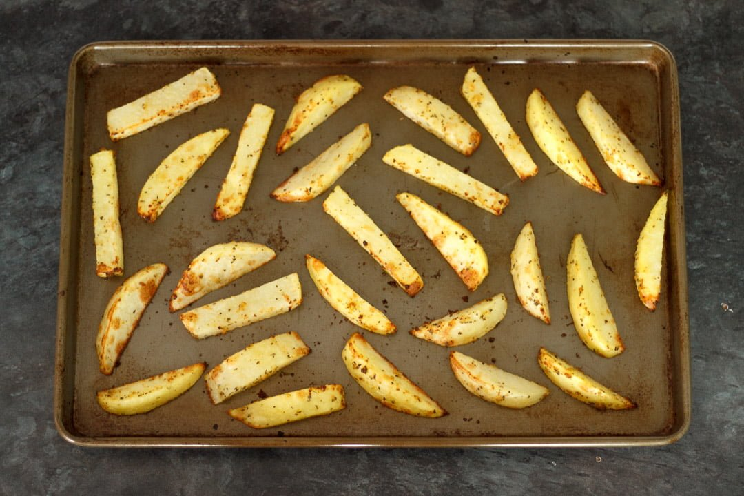 part cooked homemade wedges on a baking tray