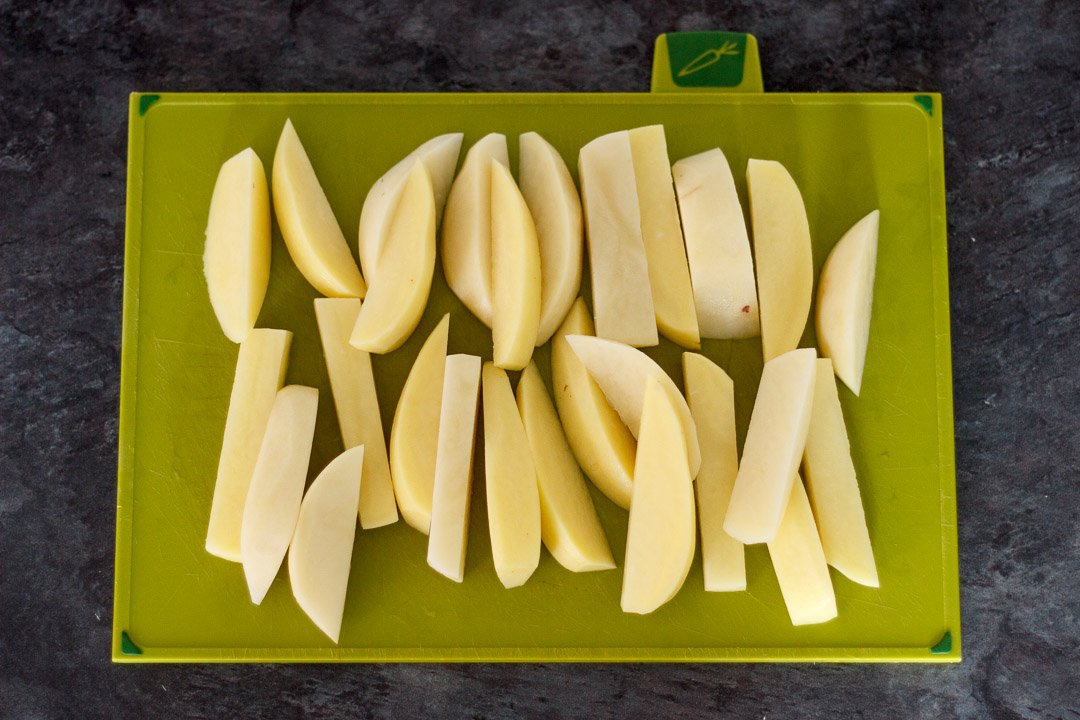 cut potato wedges on a green chopping board