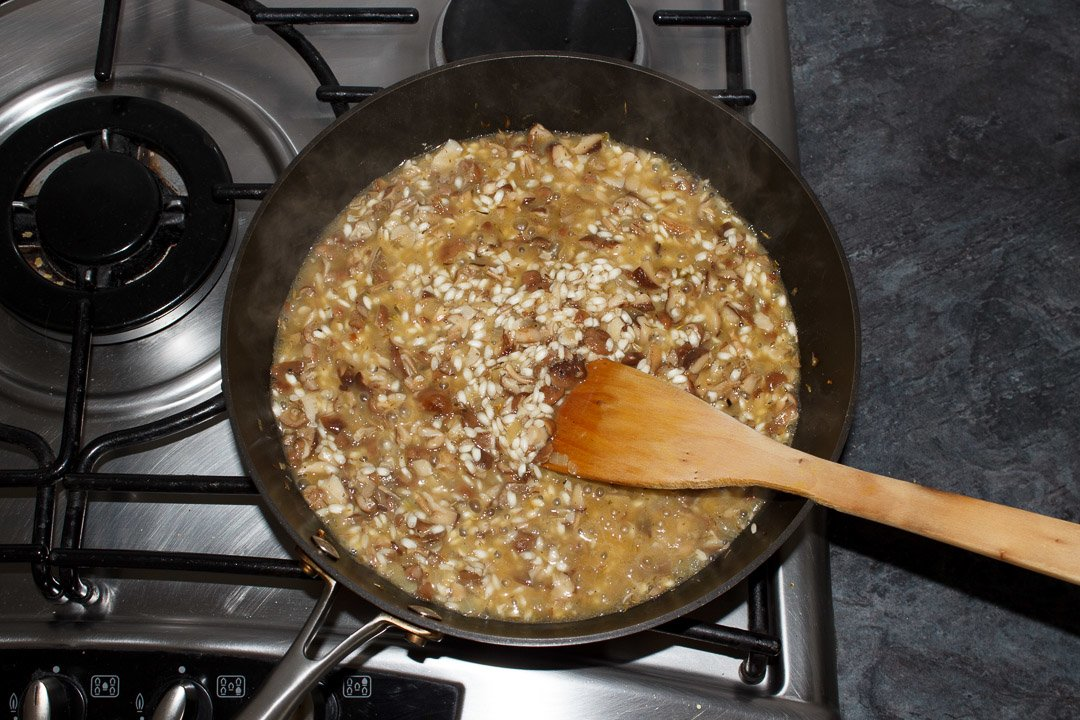 wild mushroom risotto in a large saucepan with stock beginning to be added to it