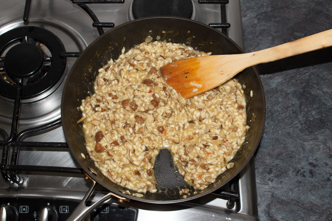 cooked wild mushroom risotto in a large saute pan with cheese melted through it