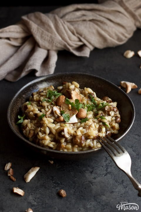 wild mushroom risotto in a bowl topped with fresh parsley