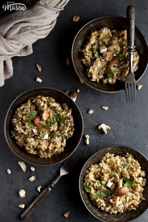 three bowls of wild mushroom risotto topped with fresh parsley