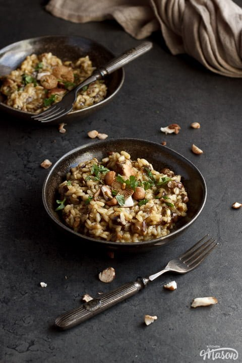 two bowls of wild mushroom risotto topped with fresh parsley
