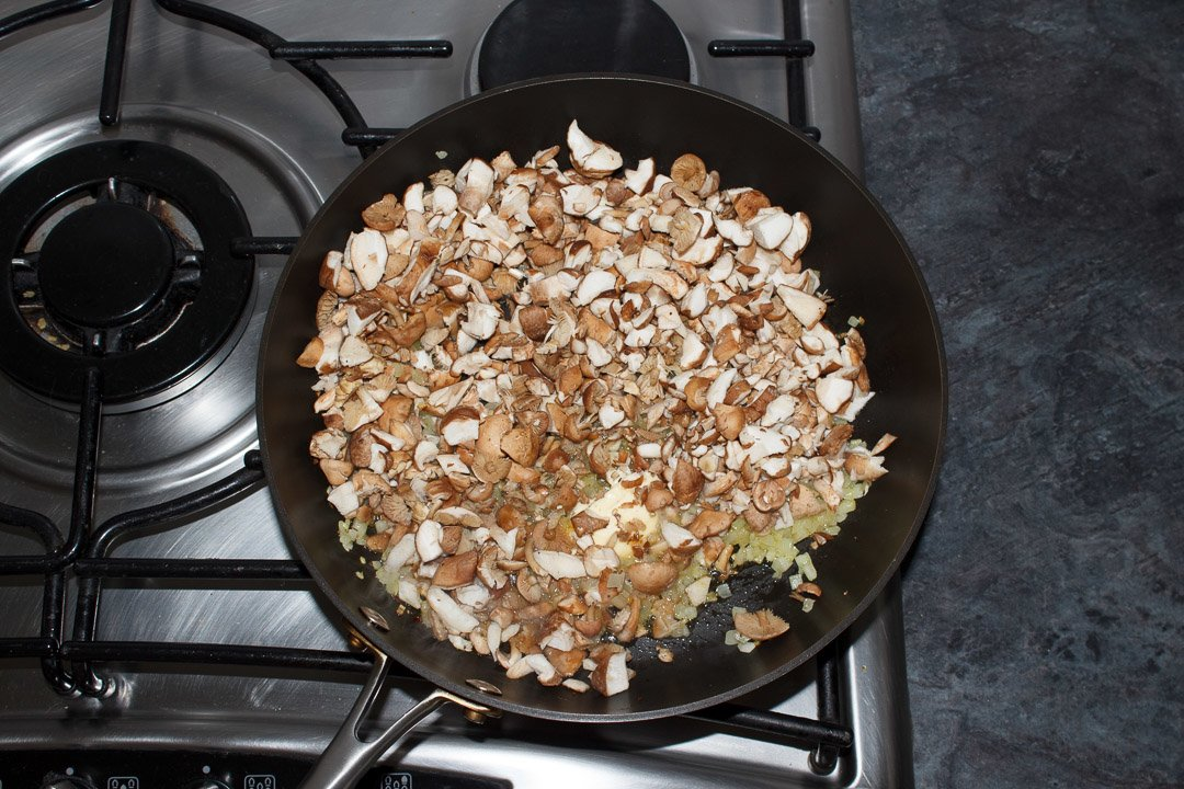 onion and mushrooms frying in a large saute pan