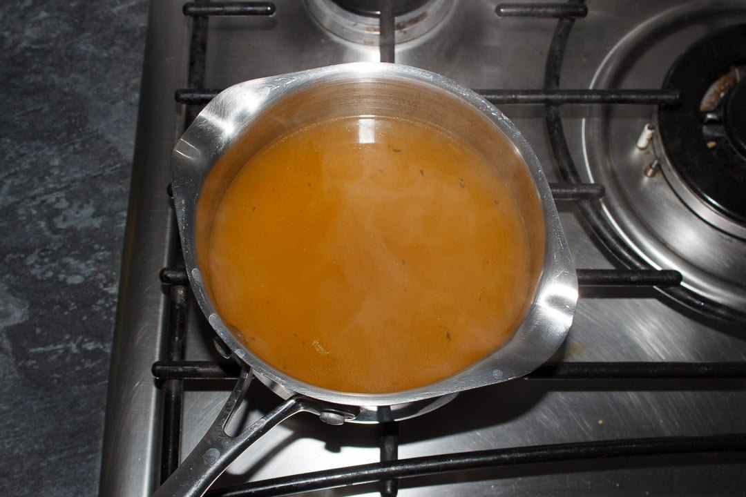 hot vegetable stock in a saucepan on the hob