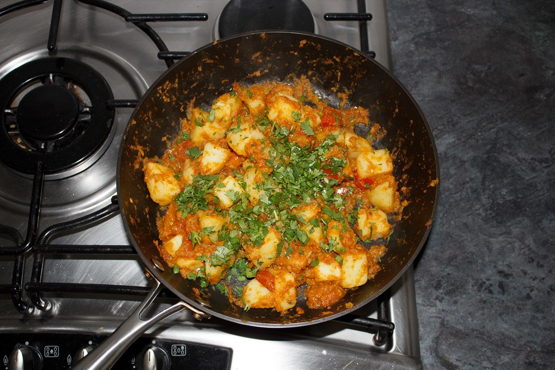 Bombay aloo in a large saute pan scattered with lots of coriander