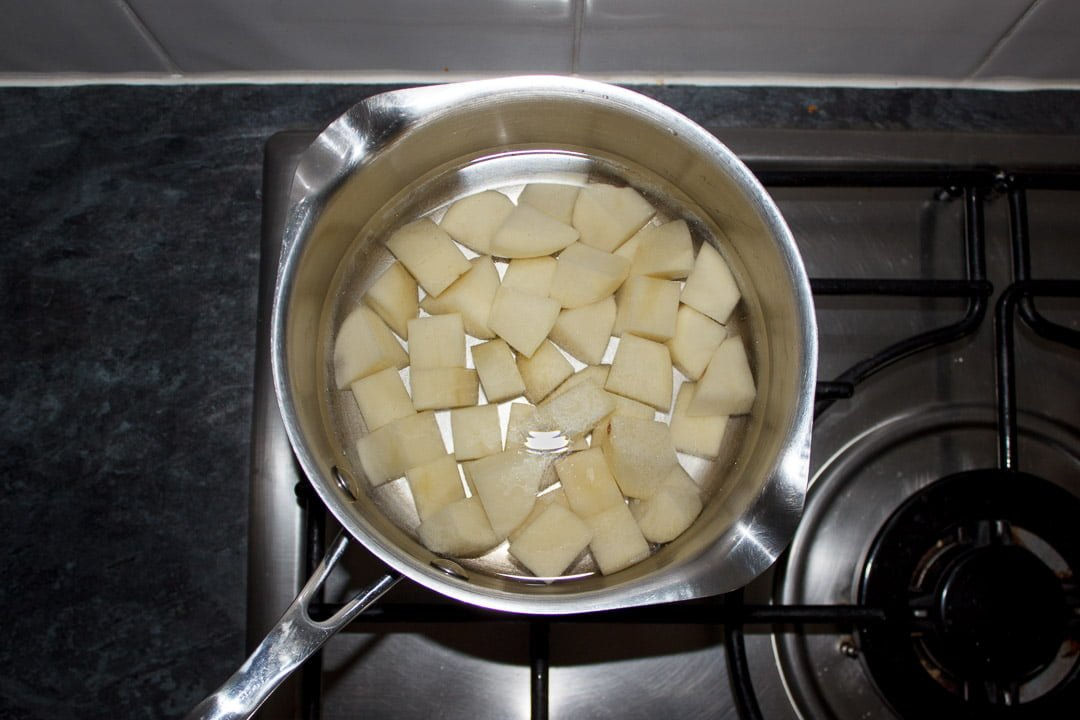 cubed potatoes in a saucepan covered in water on a stove
