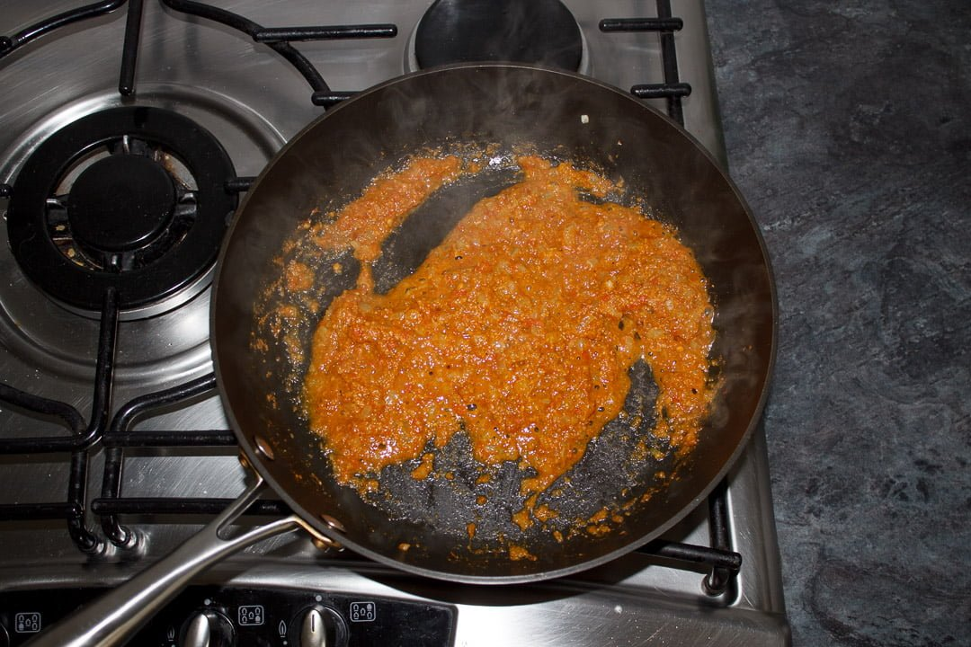 Onion frying with the tomato mixture and spices in a large saute pan