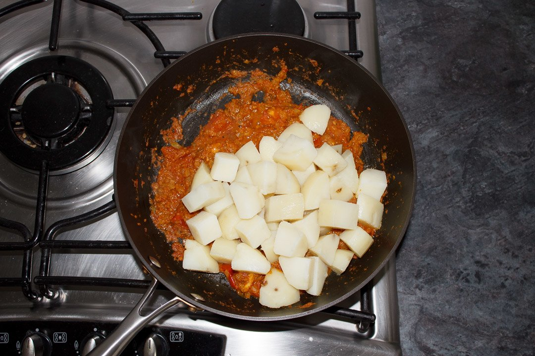 Cooked, cubed potatoes in a large saute pan with bombay aloo sauce