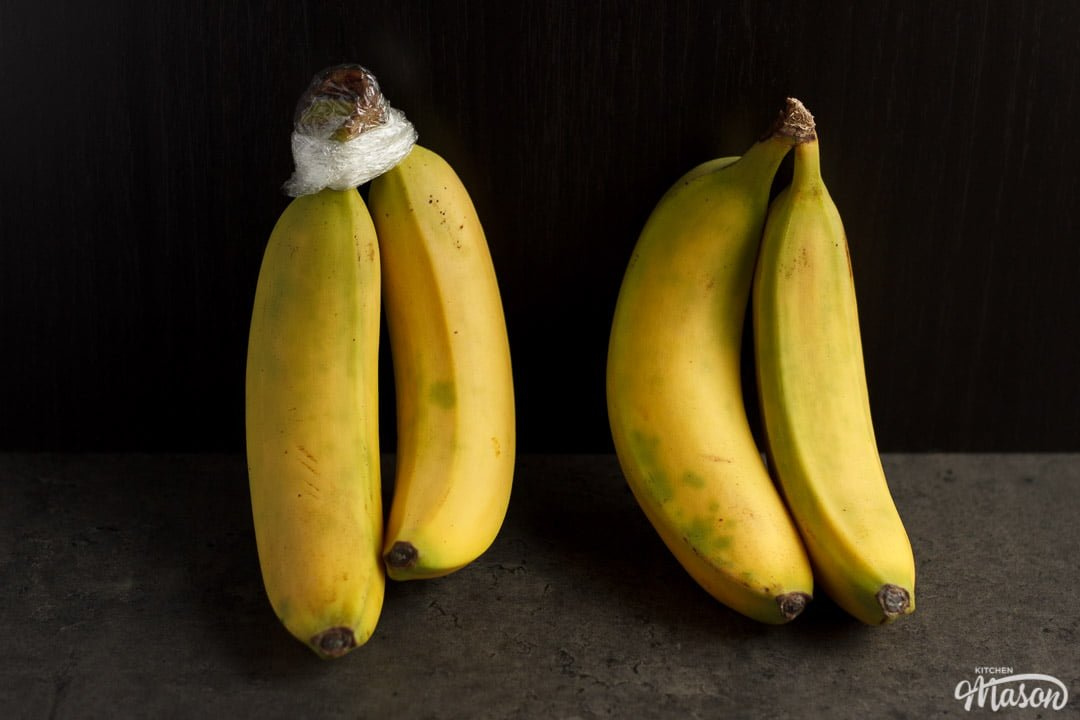 two pairs of bananas next to each other, one with the stem covered in cling film