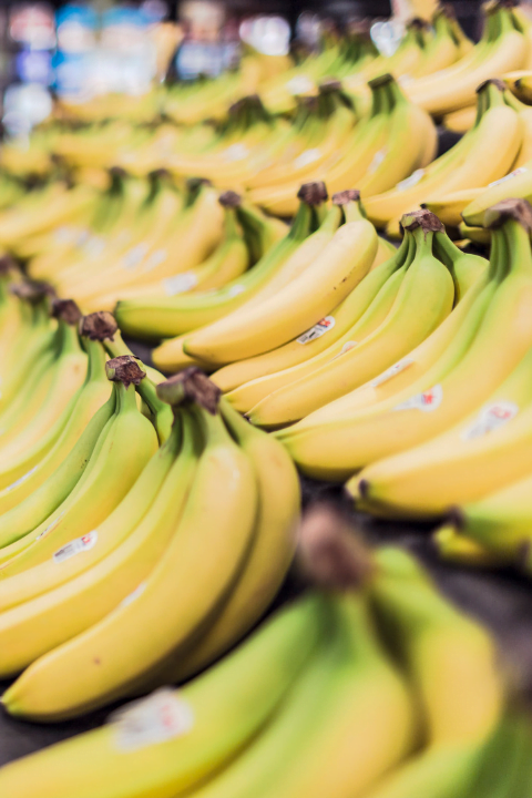 bunches of bananas on shelves at a supermarket
