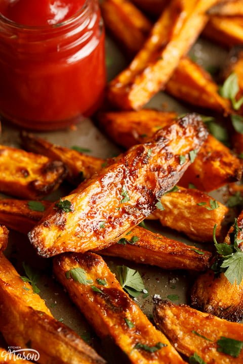Baked sweet potato wedges on a baking tray with tomato sauce
