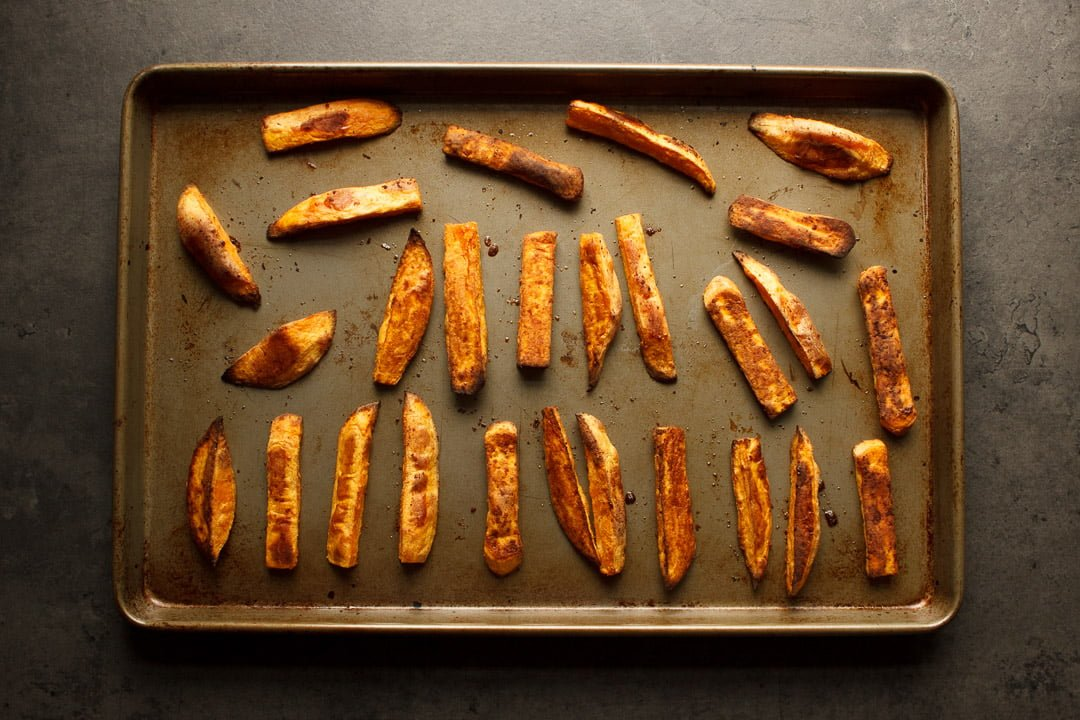 cooked sweet potato wedges spaced out on a baking tray