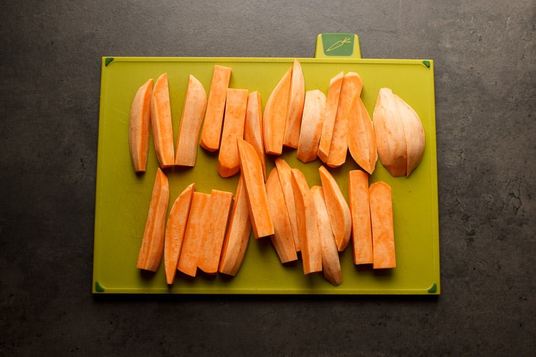 Sweet potato cut into wedges on a chopping board