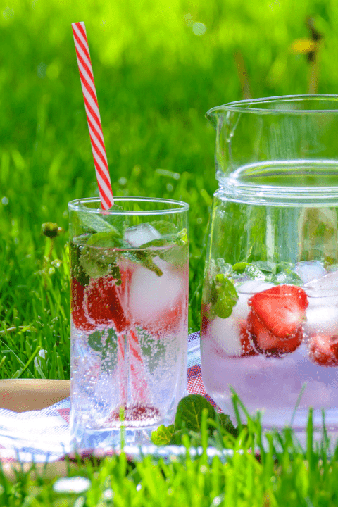 A jug and glass filled with strawberry infused water on a tray in a field