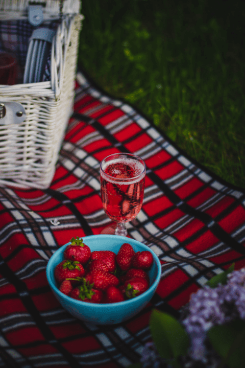 A bowl of strawberries, picnic hamper and glass of wine on a tartan picnic blanket in a field