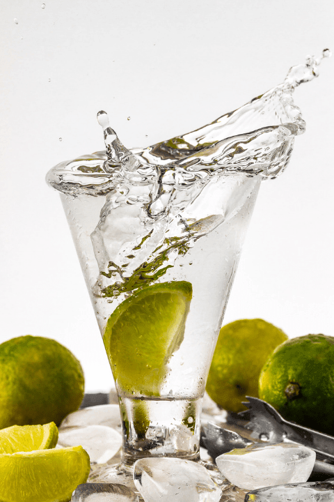 Water splashing out of a glass with limes