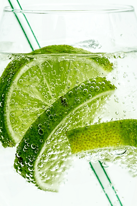 lime and a straw in a glass of water