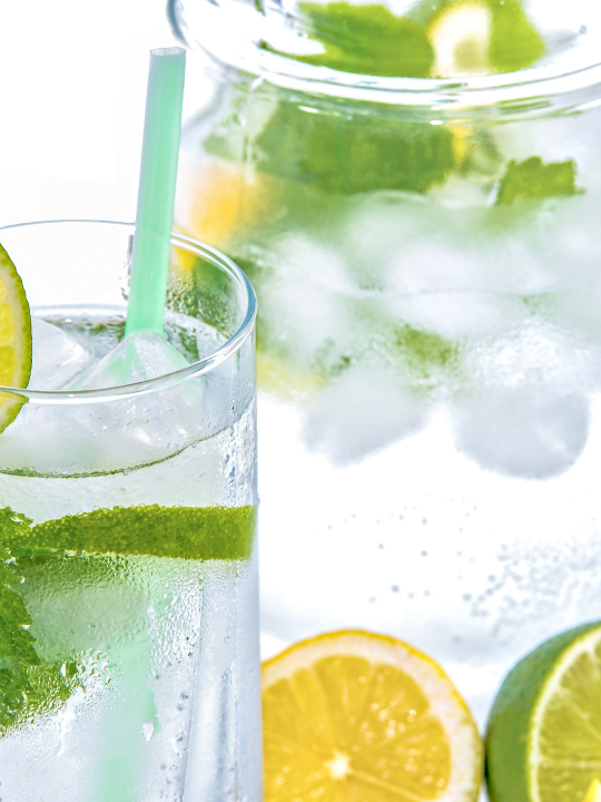 Water glasses and a jug filled with ice, cucumber and mint