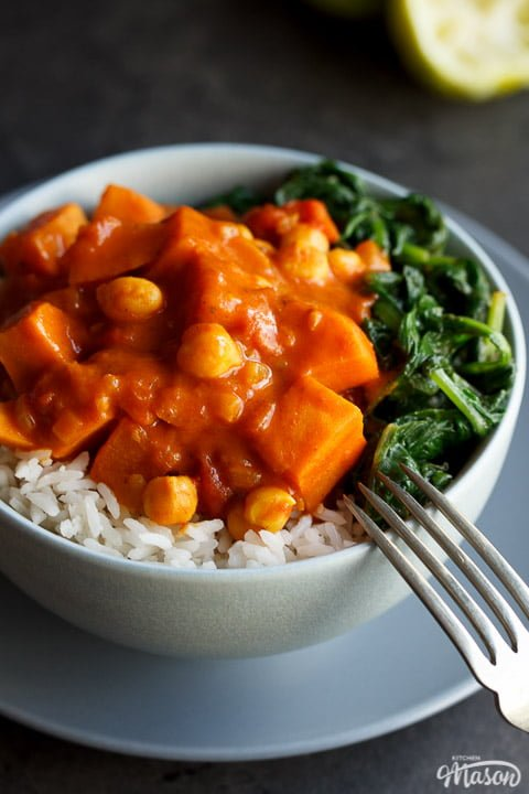 sweet potato chickpea curry in a bowl with rice and spinach