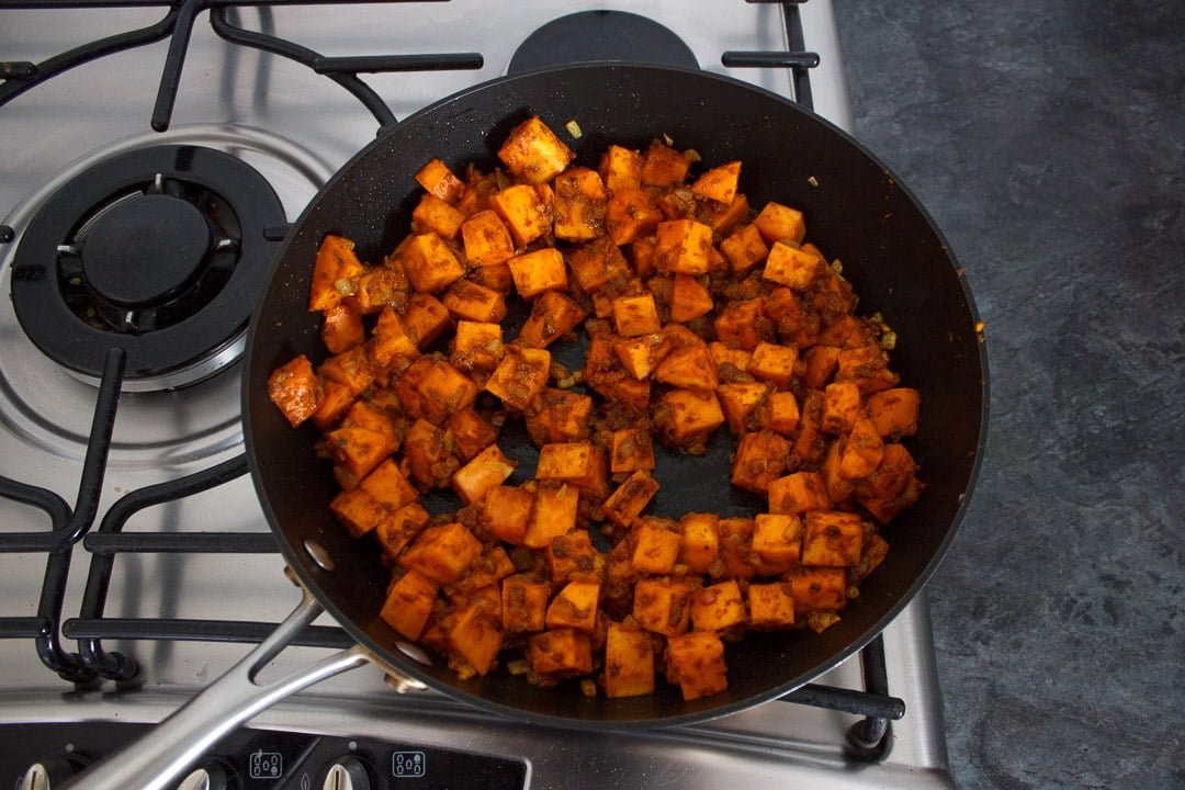 Sweet potato, onion and curry paste frying in a frying pan