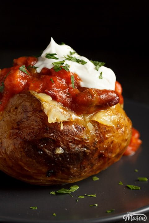 A slow cooker jacket potato on a grey plate topped with vegan chilli and vegan creme fraiche