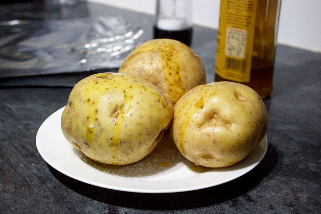 3 baking potatoes on a plate with salt, drizzled with oil