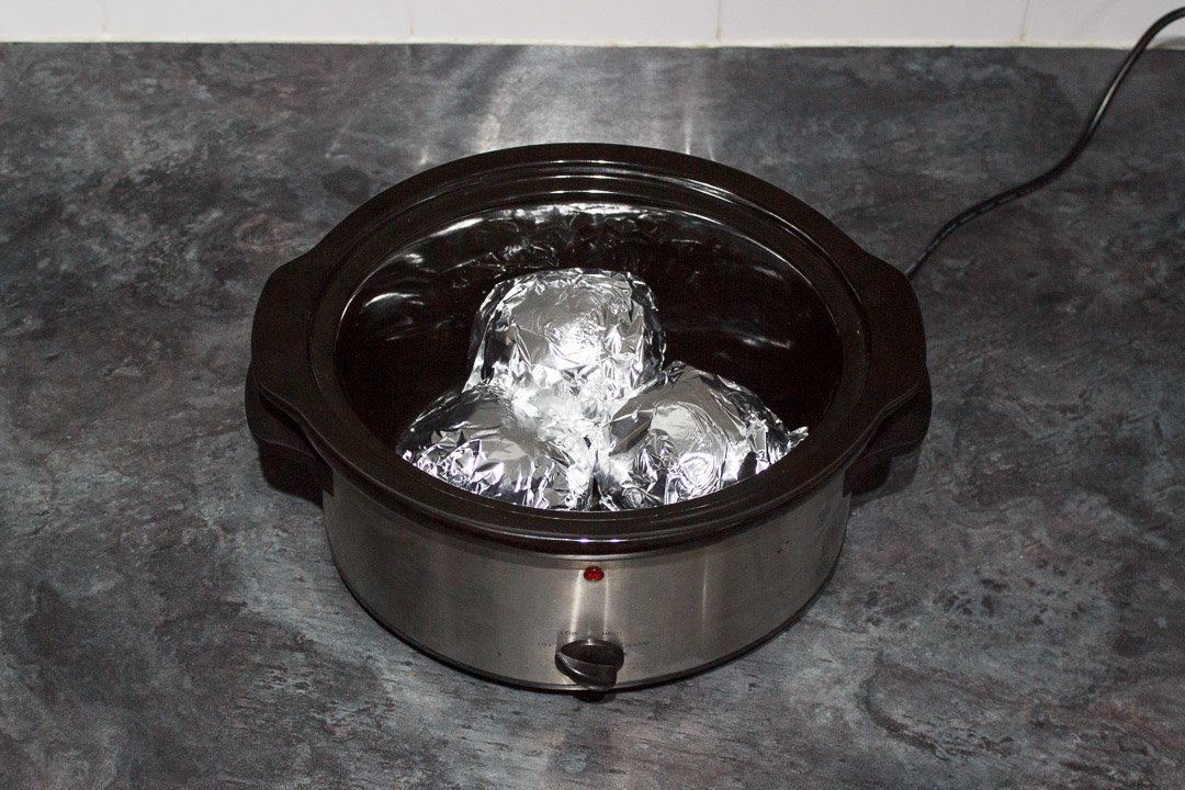 jacket potatoes wrapped in foil in a slow cooker