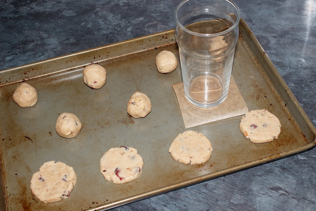Cranberry Walnut Cinnamon Cookie dough balls on a baking tray being flattened with a glass and a small square of baking paper