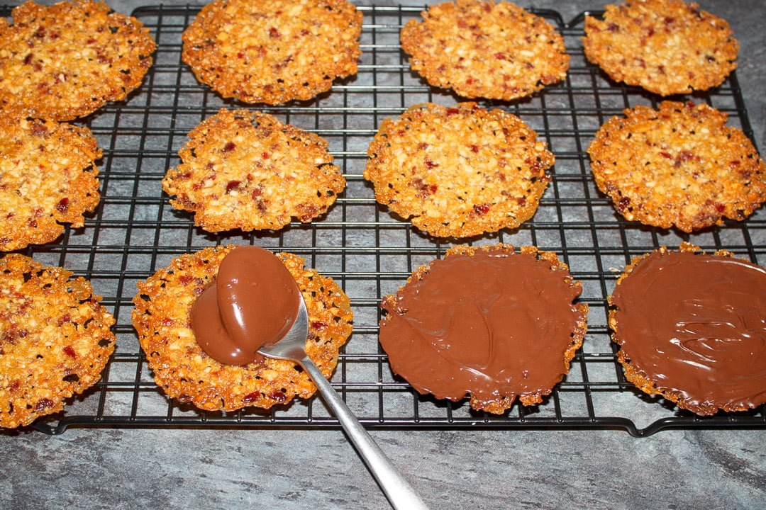 Florentine cookies on a cooling rack with dark chocolate being spread on them