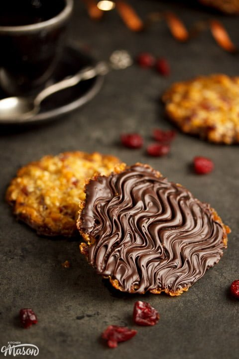 Chocolate florentines on a worktop with dried cranberries scattered around them