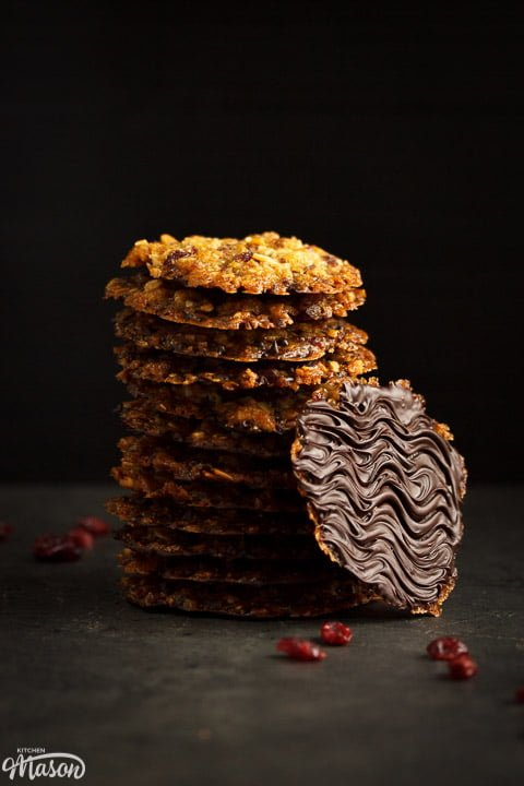 Chocolate florentines in a stack with dried cranberries scattered around them