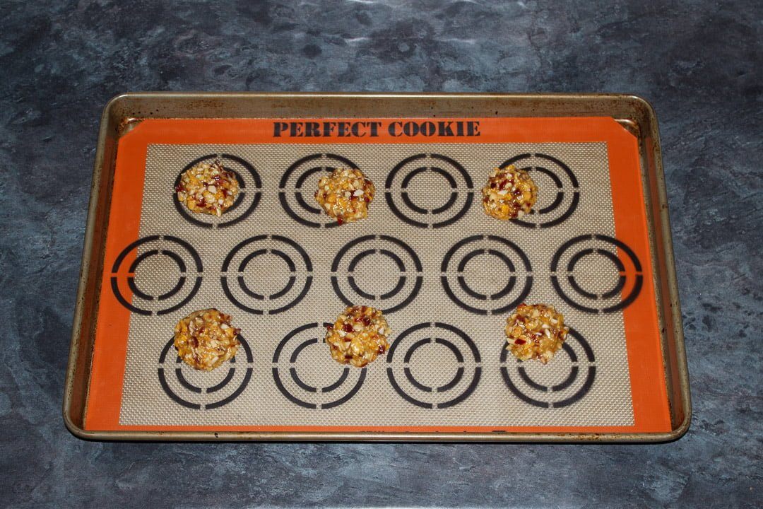 small balls of florentine cookie dough spaced out on a large baking tray lined with a silicone mat