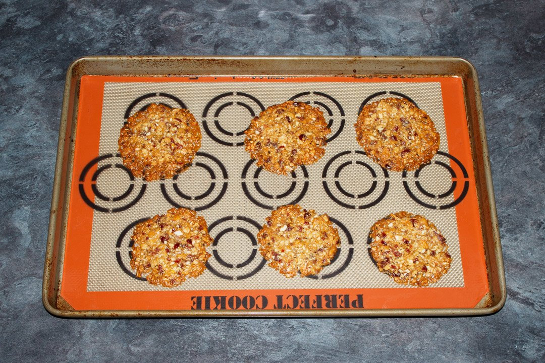 Baked florentine cookies spaced out on a large baking tray lined with a silicone mat