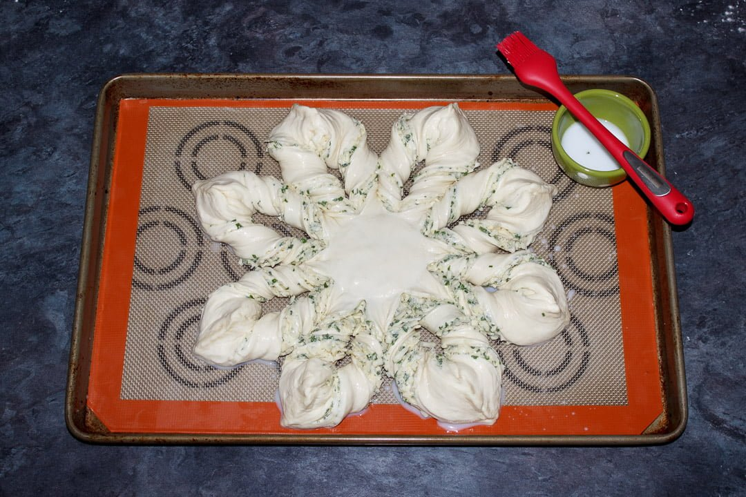 Festive star pull apart pizza dough on a lined baking tray being brushed with milk