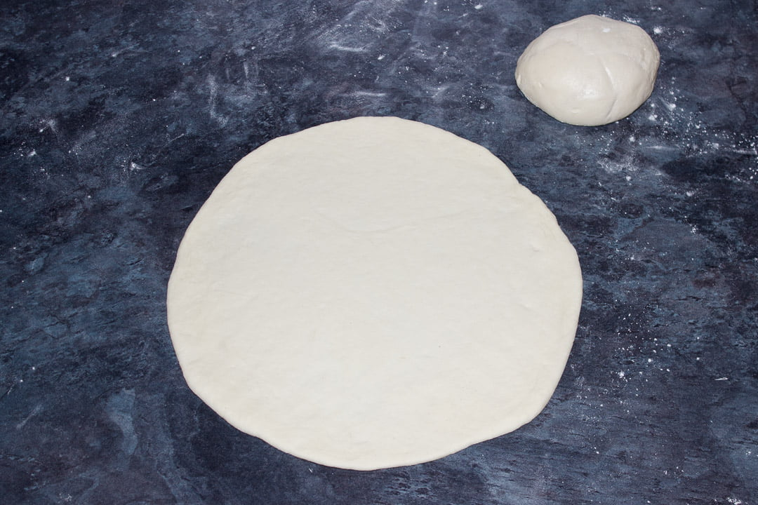 """Pizza rdough rolled out into an 11"""" circle"""