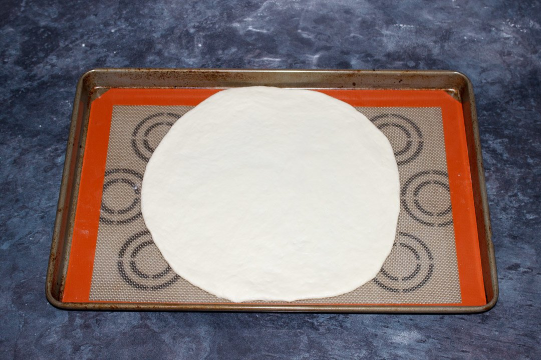 Round pizza dough on a large baking tray lined with a silicone mat