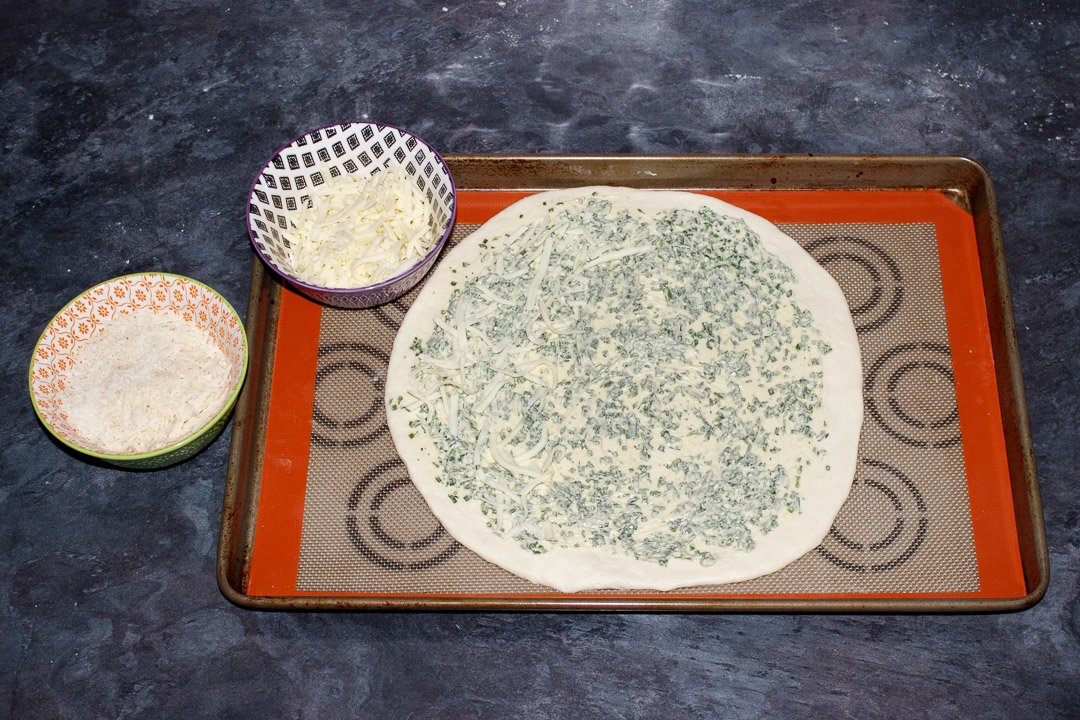 A circle of pizza dough on a large baking tray, covered in herb butter and grated cheese