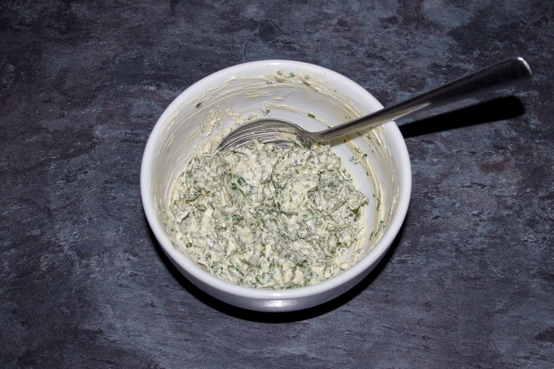 Herby butter in a bowl with a spoon