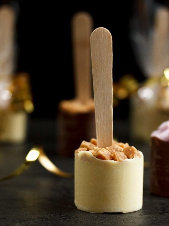 Hot chocolate sticks topped with fudge pieces and marshmallows surrounded by gold curling ribbon