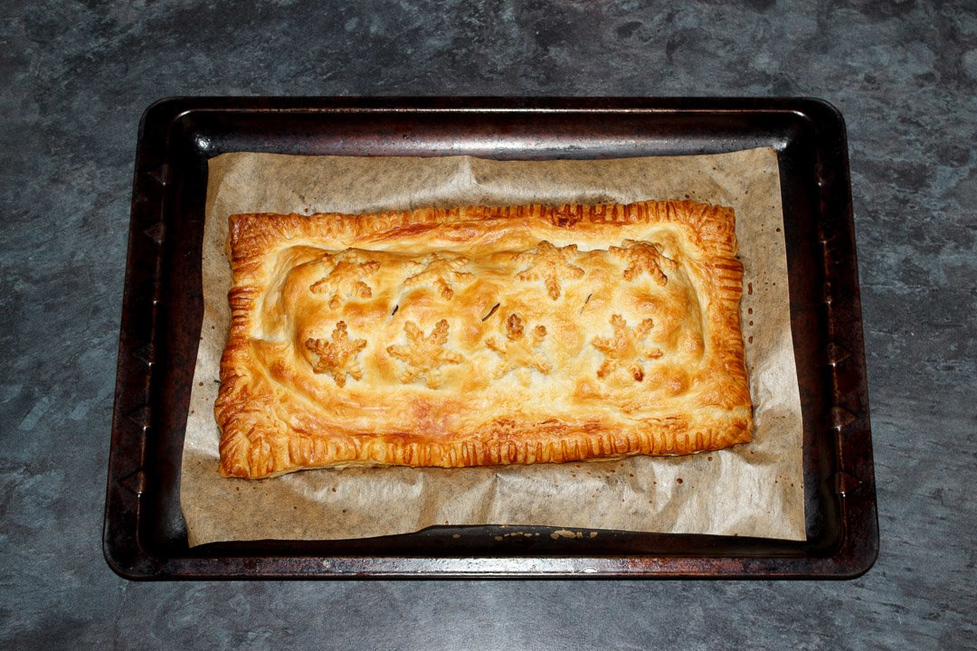 A Baked, golden vegetable wellington on a lined baking tray