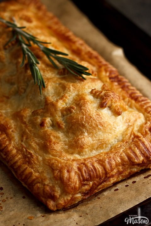 A Baked, golden vegetable wellington on a lined baking tray topped with rosemary sprigs