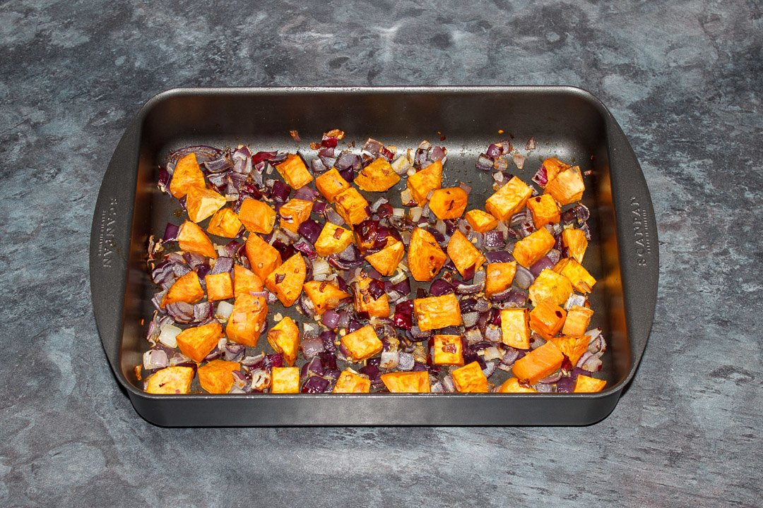 Roasted sweet potato, red onion and garlic in a roasting tray