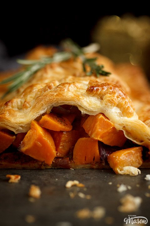 Sweet potato cubes and red onion falling out of a vegetable wellington topped with rosemary sprigs